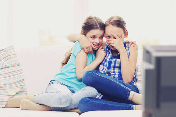 Two young girls with fear on their faces, huddling together and hugging