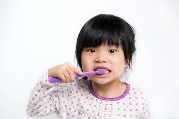 Young child, in pajamas, brushing teeth