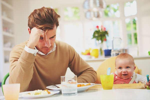 Father sitting at kitchen table with baby in high chair