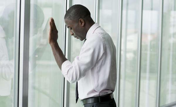 Black American leaning against window, looking dejected