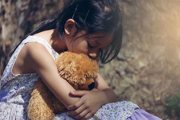 sad child separated from parents hugging teddy bear